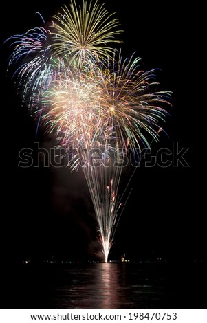 Beautiful fireworks on black sky with reflections in lake - stock photo