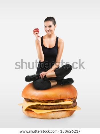 Beautiful fit girl sitting on a hamburger holding an apple - stock photo
