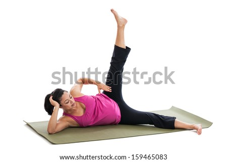 Beautiful fit Hispanic pregnant woman exercising doing leg lifts on a yoga mat on the floor isolated on white background - stock photo