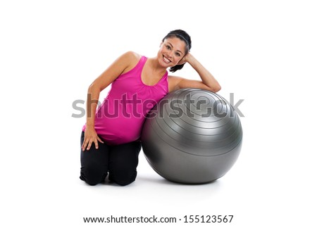 Beautiful fit Hispanic pregnant woman sitting on the floor with an exercise ball isolated on a white background - stock photo