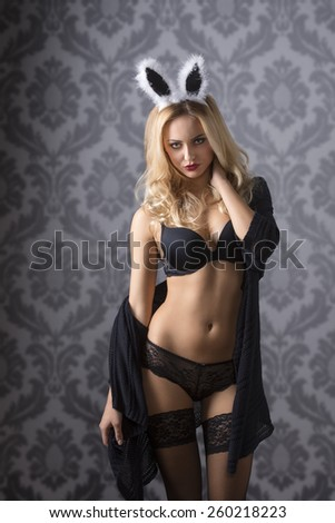 Beautiful, fit, sexy, blond woman in balck lingerie rabbit ears n the top of hear and wearing dark jumper. She has dark smoeky eye. - stock photo