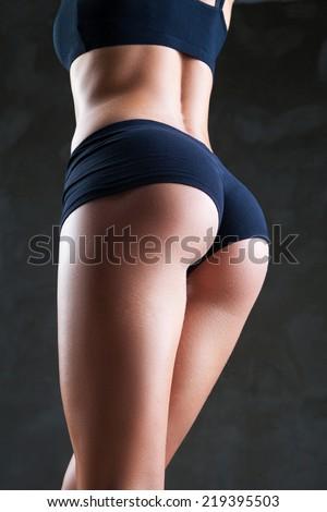 Beautiful fit, sexy female body on dark grey background - stock photo