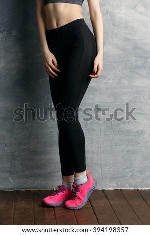 Beautiful fit, sexy female body on grey background - stock photo