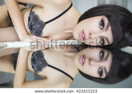 Beautiful fit slim brunette woman with black bob haircut and seductive make up in black sexy lingerie in loft home rich interior. Woman looking in the mirror - stock photo
