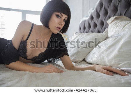 Beautiful fit slim brunette woman with black bob haircut and seductive make up in black sexy lingerie in loft home rich interior - stock photo