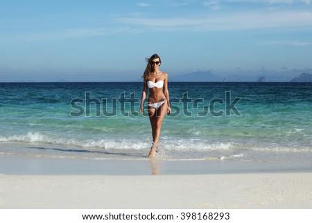 Beautiful fit woman in bikni walking from sea to tropical beach - stock photo