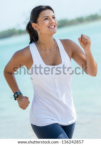 Beautiful fit woman running outdoors by the beach - stock photo