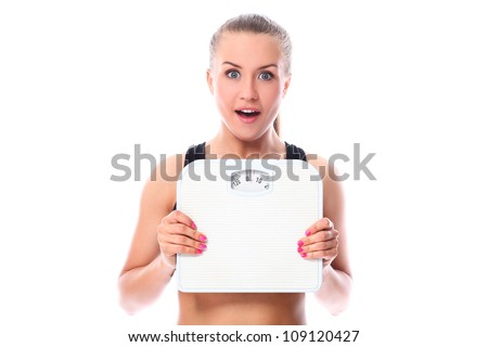 Beautiful fitness girl holding scales over white background - stock photo