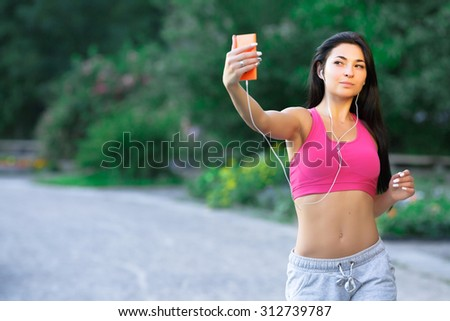 Beautiful fitness girl, with long dark hair, wearing in a pink top and gray shorts, taking selfie and listening to music with earphones, in the green park, waist up - stock photo