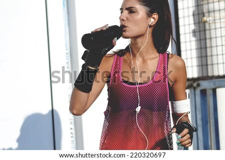 beautiful fitness woman drinking water, outdoor shot - stock photo