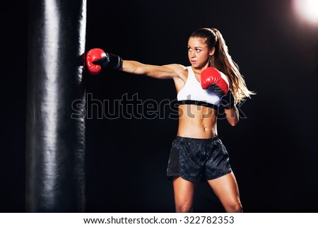 Beautiful Fitness Woman with the Red Boxing Gloves. Attractive Female Boxer Training Punching a Heavy Bag in the Gym. - stock photo