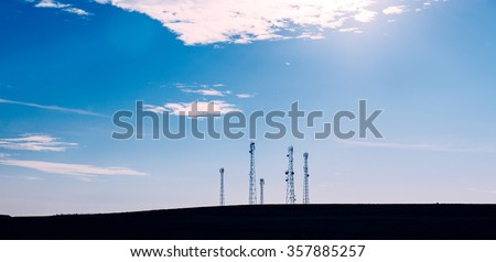 Beautiful five telecommunication mast TV antennas with blue sky and white clouds in the morning - stock photo