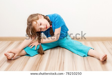 beautiful five year old girl stretching the muscles of her back and legs  at home - stock photo