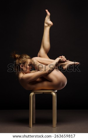 Beautiful flexible body of young woman over dark background - stock photo