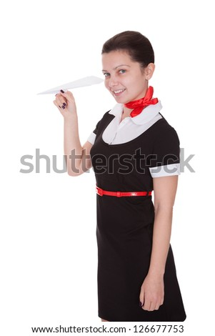 Beautiful flight attendant holding an origami paper airplane in her hand conceptual of airline flight and travel isolated on white - stock photo