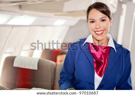 Beautiful flight attendant in an airplane cabin smiling - stock photo