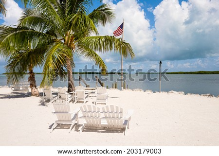 Beautiful Florida Keys along the shoreline with lounge chairs and gulf view. - stock photo