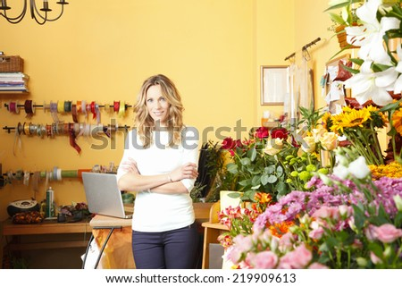 Beautiful florist standing in front of flower shop facade. Small business. - stock photo