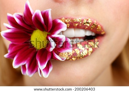 Beautiful flower in teeth, close up - stock photo