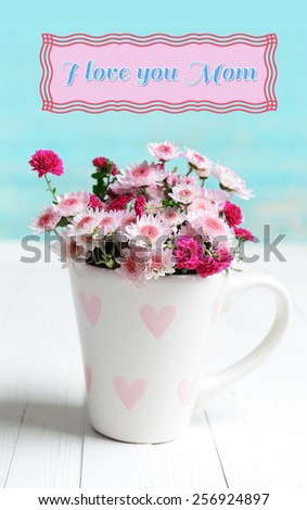 Beautiful flowers in cup on table on light blue background, Mother's Day concept - stock photo