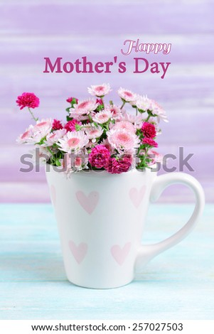 Beautiful flowers in cup on table on lilac background, Mother's Day concept - stock photo
