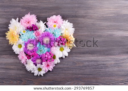 Beautiful flowers in heart shape on wooden background - stock photo