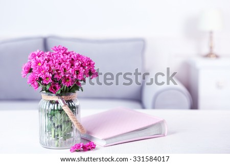 Beautiful flowers in vase on table in room - stock photo