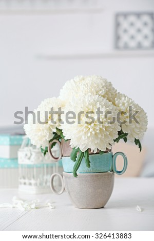 Beautiful flowers in vase on table in room on bright background - stock photo