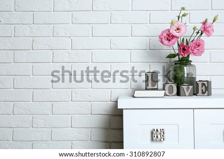 Beautiful flowers in vase with word Love on brick wall background - stock photo