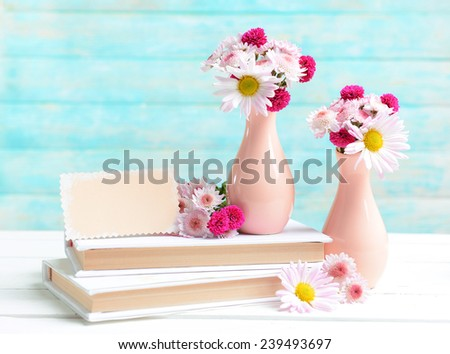Beautiful flowers in vases on table on light blue background - stock photo