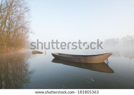 Beautiful foggy sunrise with old rusty boats on a lake - stock photo
