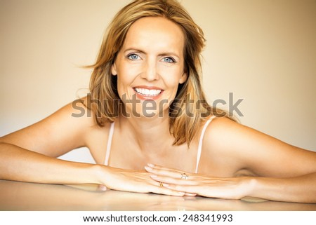 Beautiful forty year old woman posing in warm-colored environment.  - stock photo