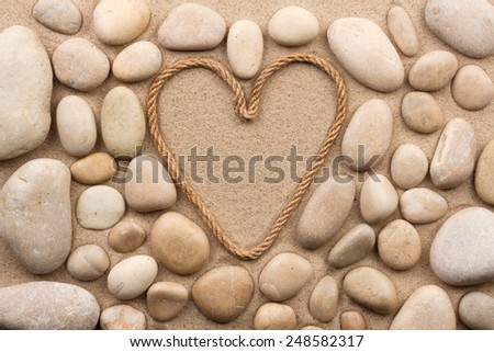 Beautiful frame of rope in the form of heart with white stones, on the sand - stock photo