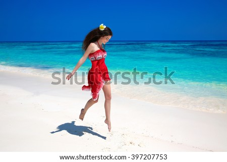 Beautiful free young woman jumping on the exotic sea, brunette smiling girl in red dress running on tropical beach with white sand. Enjoyment. Lifestyle. Freedom. Good life. Travel.  - stock photo