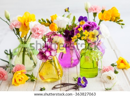 Beautiful fresh flowers in glass bottles on the wooden table - stock photo