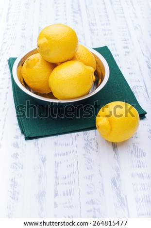 Beautiful fresh lemons in an iron bowl. Ripe fruit. Healthy food. Vegetable diet. Wooden board rustic - stock photo
