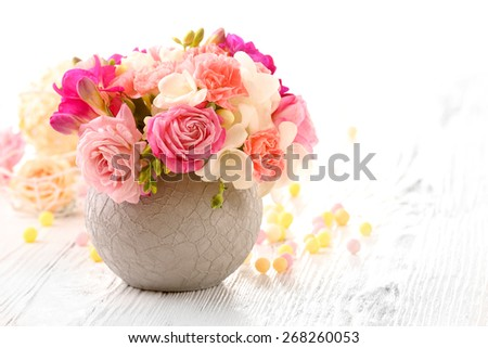 Beautiful fresh spring flowers in pot on wooden table, closeup - stock photo