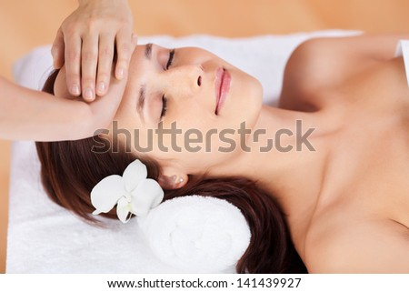 Beautiful fresh woman having facial massage in spa centre - stock photo
