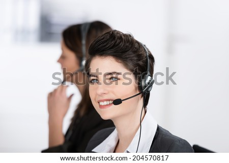 Beautiful friendly call center operator wearing a headset sitting looking up into the air as she listens to the conversation with a client with a smile - stock photo
