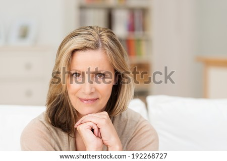 Beautiful friendly middle-aged woman sitting looking directly at the camera with a smile and her chin resting on her clasped hands - stock photo
