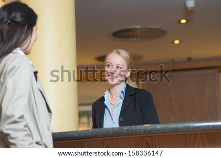 Beautiful friendly smiling receptionist behind the service desk in a hotel lobby helping an attractive female guest indicating with her hand the way to her accommodation - stock photo
