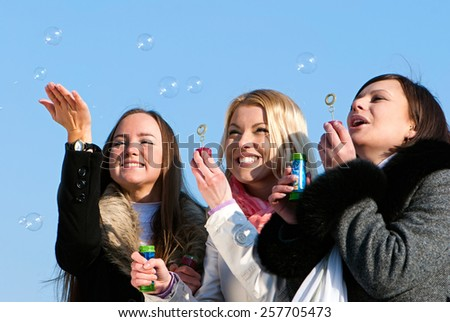 beautiful friends blowing bubbles in the nature - stock photo