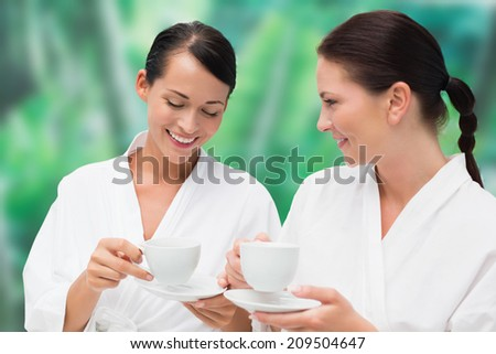 Beautiful friends in bathrobes drinking herbal tea on blue and green background - stock photo