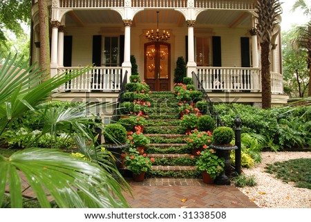 Beautiful front stairs and yard of historic colonial home with flowers and ivy - stock photo