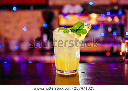 beautiful frozen cocktail glass with ice, mint and pineapple on a dark wooden bar counter, bokeh bright background - stock photo