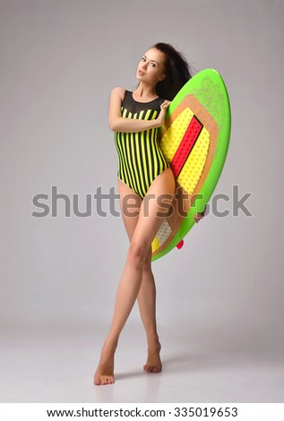 Beautiful full body brunette young woman walking with long hair and surfboard over a gray background - stock photo