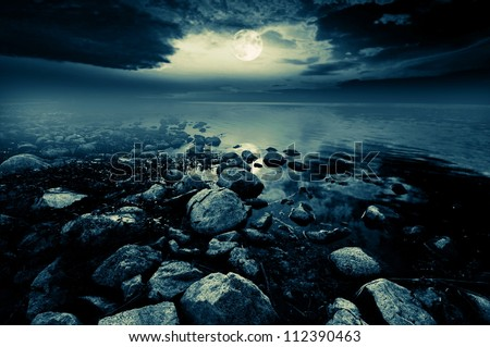 Beautiful full moon reflecting in a lake - stock photo