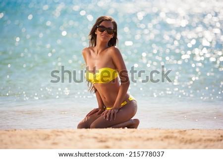 beautiful fun and joy brunette woman in yellow bikini posing  tropical  blue sea water has sports and tan body - stock photo