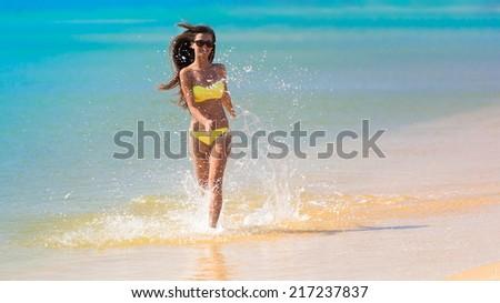 beautiful fun and joy brunette woman in yellow bikini run tropical  blue sea water has sports and tan body - stock photo