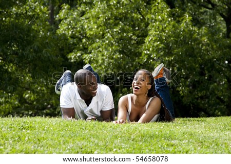 Beautiful fun happy smiling laughing African American couple joking laying on grass in park, wearing white shirts and blue jeans. - stock photo